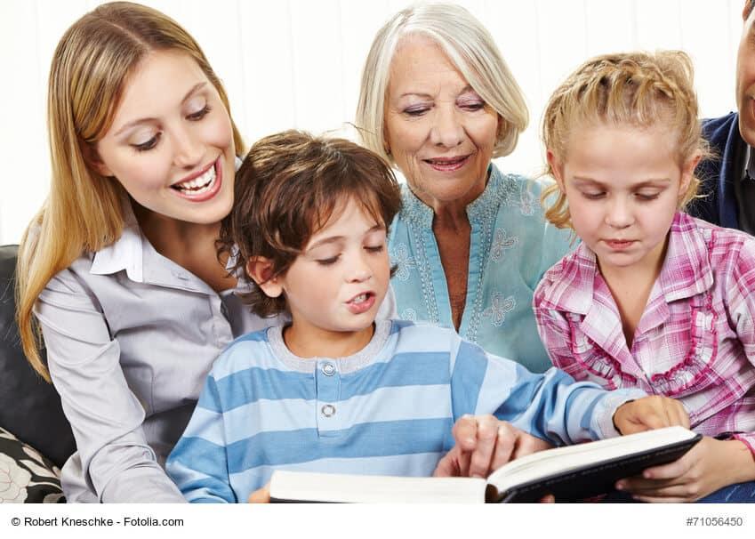 Familie in drei Generationen liest Buch